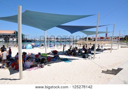 HILLARYS,WA,AUSTRALIA-JANUARY 22,2016: Foreshore with families, shelters and in the swimming cove at Hillarys Boat Harbour, in Hillarys, Western Australia.