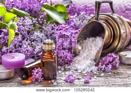 Essential oils and bath salt with a background of lilac