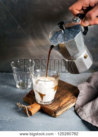 A glass of coffee with ice cream on a rustic wooden board. Drink is poured from a steel Italian Moka pot held by man's hand, grey background