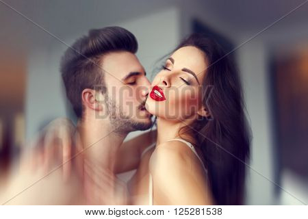 Macho young man kissing sexy milf woman neck