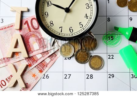 Tax time and alarm clock with money, marker and calendar