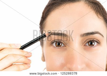 Close up of woman painting her eyebrows with eyebrow pencil. Isolated on white background.