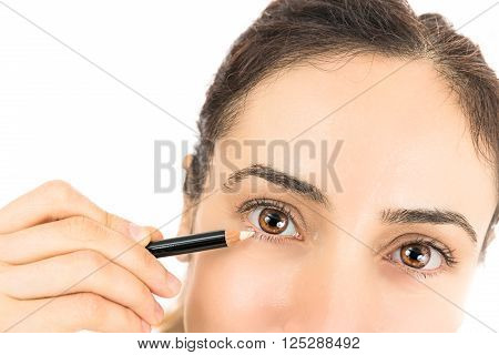 Close up eyes of a woman when using eyeliner. Isolated on white background.