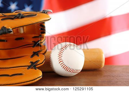 Baseball, glove and bat on background of American flag. Popular sport concept