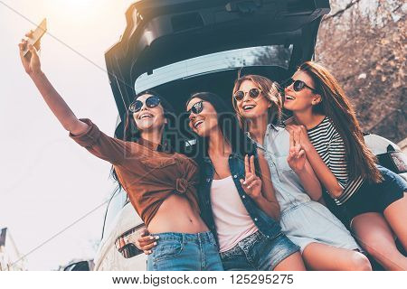 Just one selfie before road trip! Four beautiful young cheerful women making selfie with smile while standing near car trunk