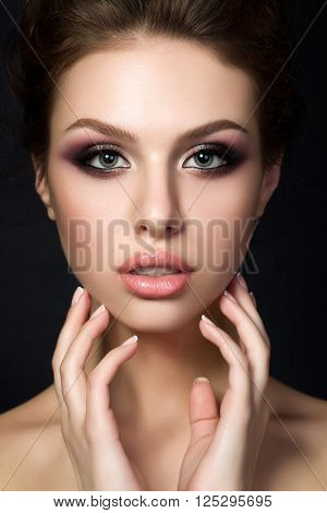 Portrait of young beautiful woman with evening make up touching her face over black background. Multicolored smokey eyes. Luxury skincare and modern fashion makeup concept. Studio shot.