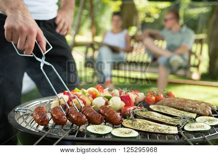 Grilling sausages and vegetables on bbq party