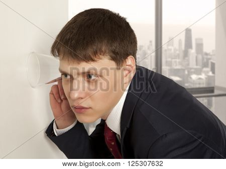 Businessman spying by listening through wall with glass