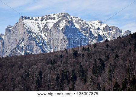 Bucegi mountains in winter with the Heroes Cross Monument on top of Caraiman Peak. The Cross is dedicated to the romanian heroes of World War I.