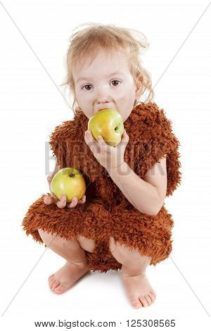 Little funny Neanderthal boy in a suit with a dirty face eating an apple. Humorous concept ancient caveman. Isolated on white.