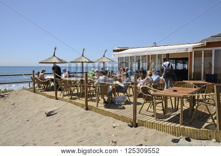 MARBELLA, SPAIN -APRIL 9, 2016: People having lunch at sun in the terrace of a beach bar in Marbella a city in southern Spain belonging to the province of Malaga Andalusia Spain