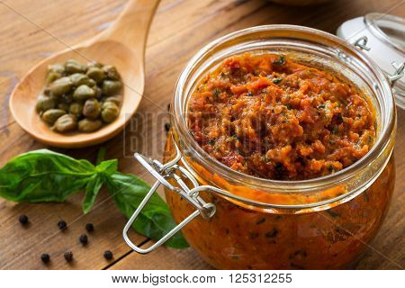 Pesto with dry tomatoes and almonds in a glass jar on a wooden table