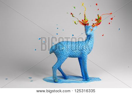Blue deer with colorful magic horns standing in pound of blue paint