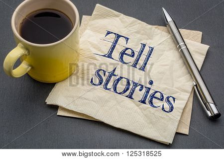 Tell stories advice or reminder - handwriting on a napkin with cup of coffee against gray slate stone background