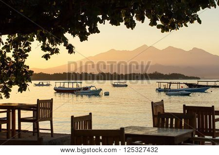 Restaurant and boats on the coast of Gili Travangan island with a sunrise view of Gunung Rinjani volcano on Lombok island, Indonesia.