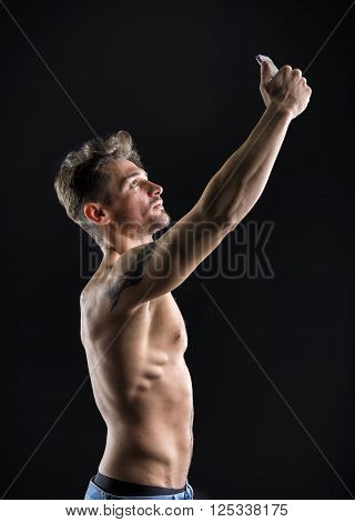 Handsome shirtless muscular young man using cell phone to take selfie picture, on dark background