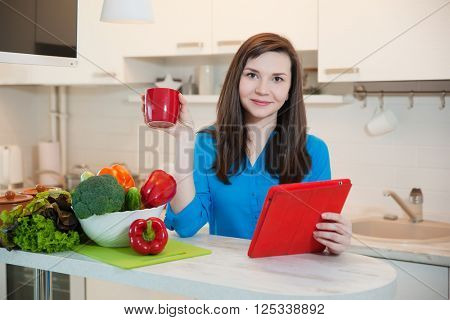 Woman using a tablet computer while drinking tea in her kitchen