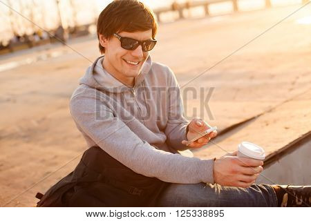 Young man holding mobile phone, using smartphone on sunny street