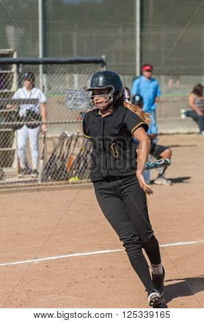Teenager in black uniform moving on the infield.