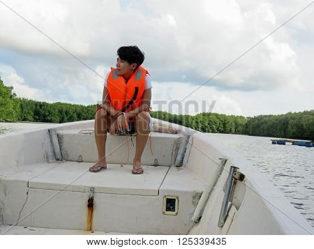 Young Filipino woman relaxing on boat while on Bujang Sungai Lebam River Cruise Of Malaysia