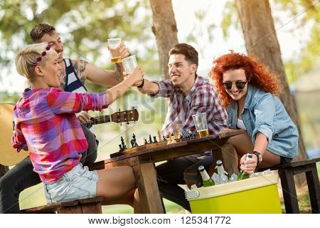 Cheerful society toast with glasses of cold beer in forest