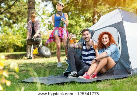 Young guy and curly ginger woman toast with glasses of beer in front of tent at camping in woods