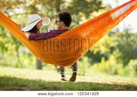 Young man and girl in orange hammock from back in beautiful forest