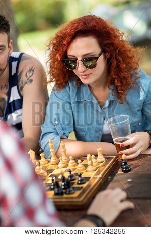 Young curly female play chess at summer camp in forest