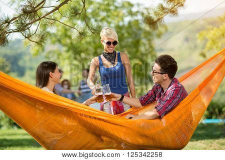 Young couple, male and female in hammock in nature toast with beer with female friend