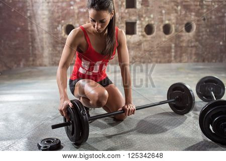 young fitness woman preparing to lift some heavy weights