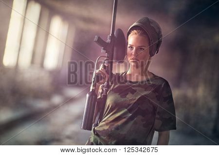 Attractive young woman with marker gun, paintball sport and leisure