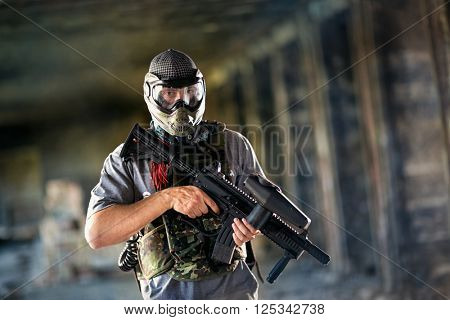 Paintball player with protective mask and gun