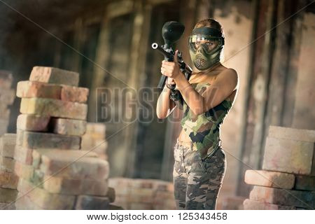 woman in camouflage  uniform with mask, paintball game in runs