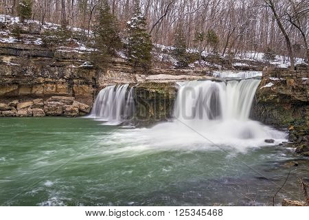 Water spills over Upper Cataract Falls a waterfall in Owen County Indiana as late winter snow melts into spring.