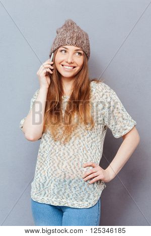 Smiling stylish woman talking on the phone and looking away over gray background