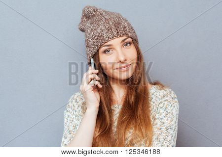 Happy woman talking on the phone over gray background