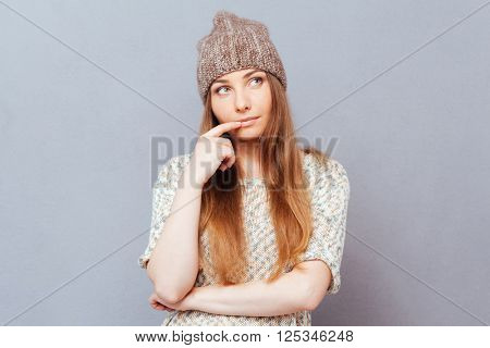 Thoughtful stylish woman looking away over gray background