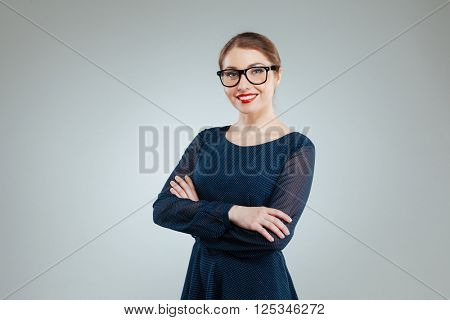 Smiling woman in glasses standing with arms folded isolated on a white background and looking at camera