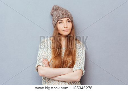 Serious woman standing with arms folded over gray background