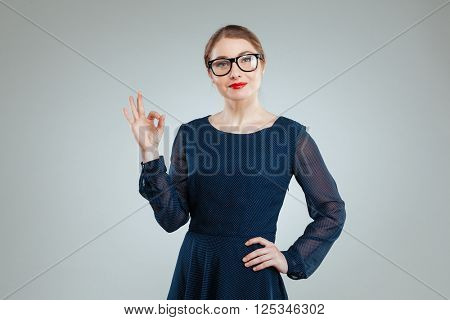 Beautful woman in glasses showing ok sign with fingers isolated on a white background