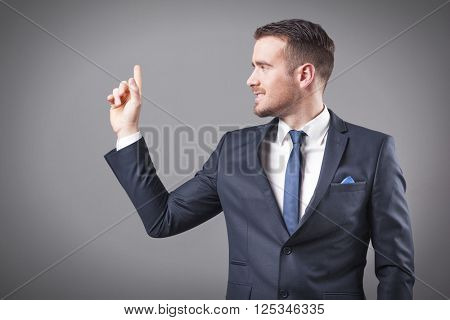 Handsome smiling business man pointing at copy space on grey background