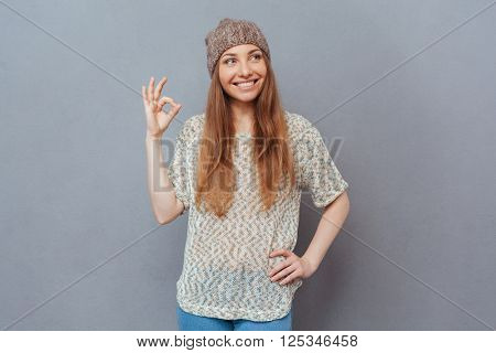 Smiling woman showing ok sign with fingers over gray background