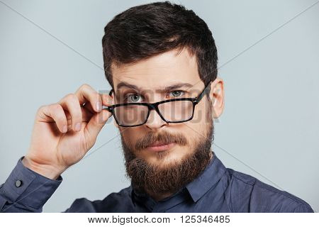 Closeup portrait of a serious man in glasses looking at camera isolated on a white background