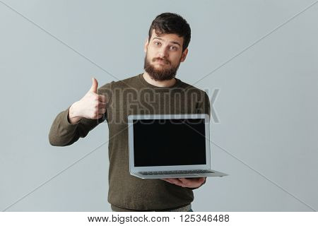 Casual man showing blank laptop computer screen and thumb up over gray background