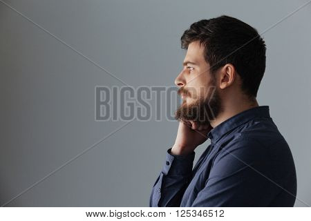 Side view portrait of a pensive man standing over gray background