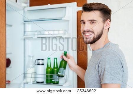 Smiling attractive young man taking bottle of beer from refrigerator on the kitchen