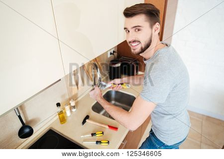 Smiling handsome young man plumber fixing water tap with wrench