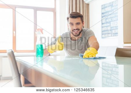 Happy bearded man cleaning his flat and showing thumbs up