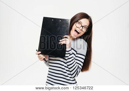 Cheerful woman peeking from clipboard isolated on a white background