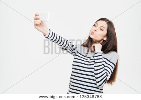 Funny woman making selfie photo on smartphone isolated on a white background